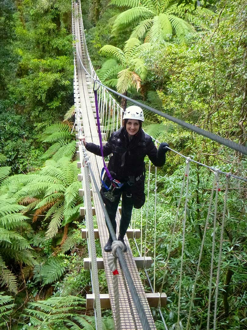 Me standing on a swing bridge smiling while walking to the next platform to go zip lining in Rotorua, New Zealand