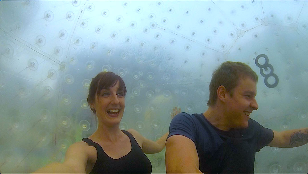 Casey and I inside the OGO Zorbing ball looking excited as it starts to roll down the zigzag path on the hill