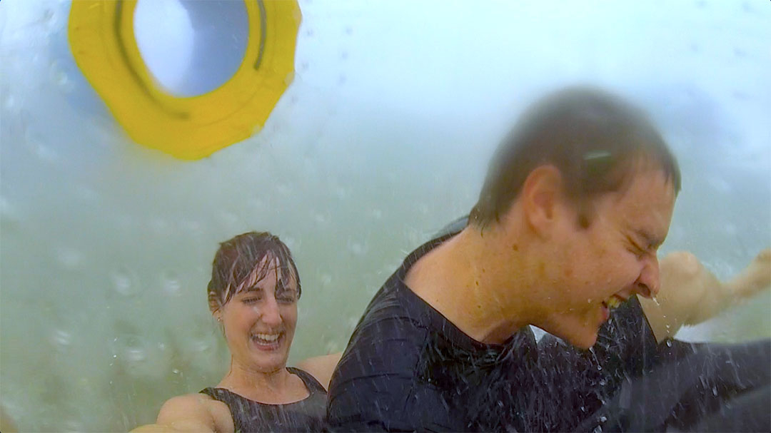 Casey and I drenched in water while Casey falls on top of me as we get thrown about inside the OGO Zorbing ball on the zigzag path