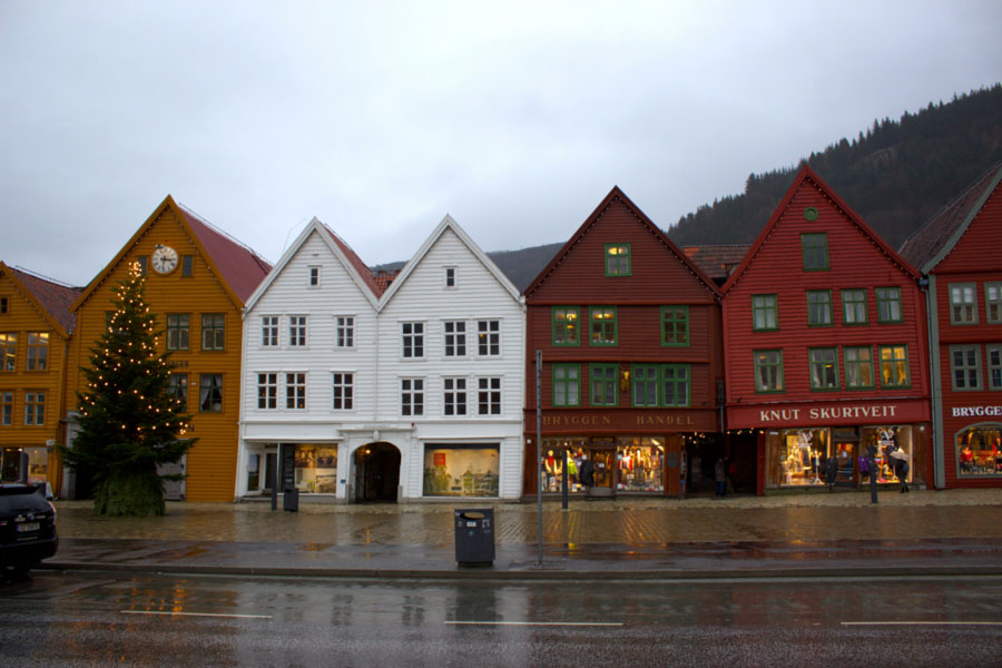 Colourful UNESCO buildings lined up side by side touching each other in Bergen, Norway during a rainy winter day