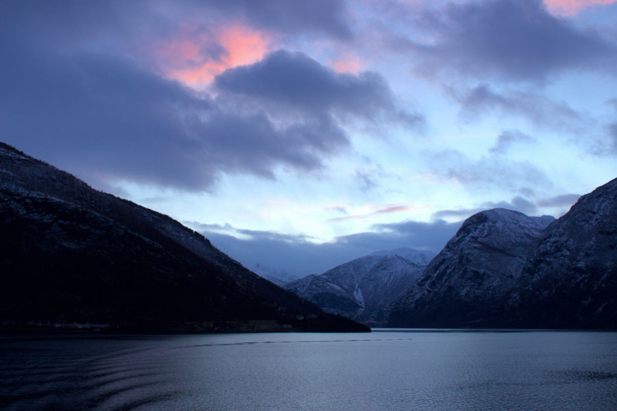 Beautiful view of Norwegian Fjords from the back of the ferry during sunset, with pretty pink clouds in the sky during winter in Norway
