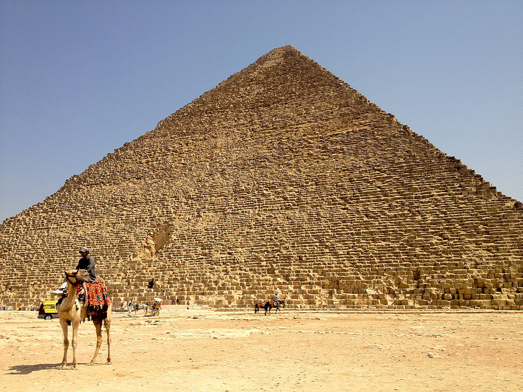 Grand Pyramid of Giza in Egypt with a man riding a camel in the foreground on a hot summer's day