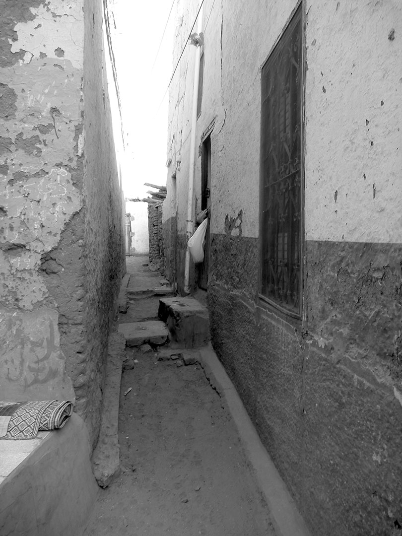 Quiet black and white walkways in a Nubian Village between old mud brick buildings