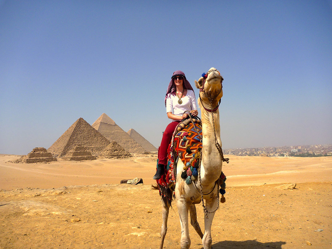 Me sitting on Charlie the camel in front of the Great Pyramids of Giza in Egypt