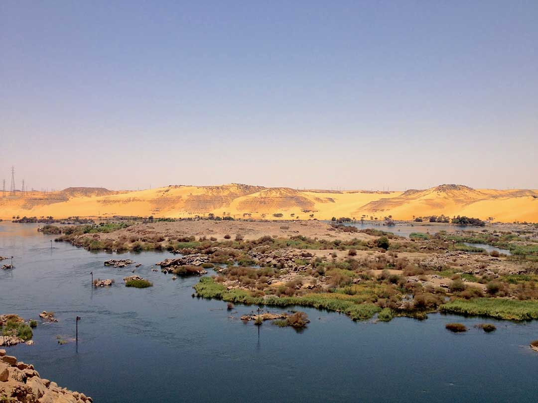 A small lake with moss covered rocks and sand dunes in the background in Giza, Egypt during Summer