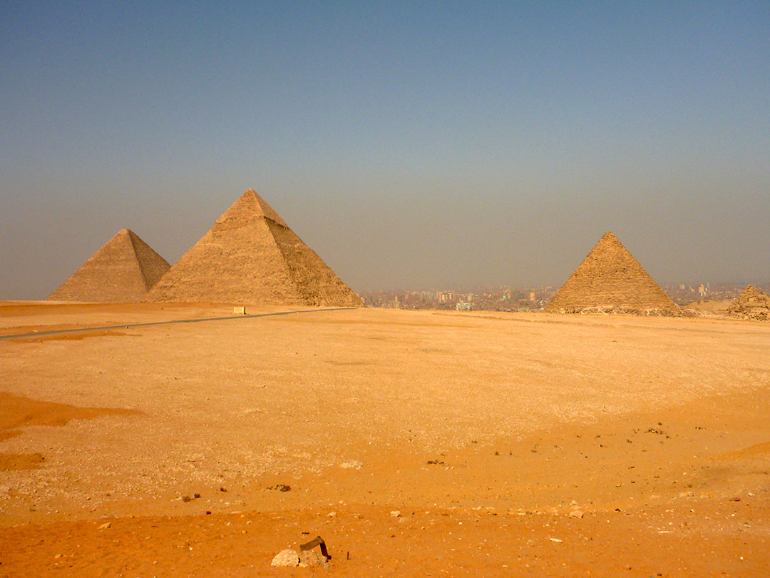 The Pyramids of Giza with the city in the background on a dusty hot summer day