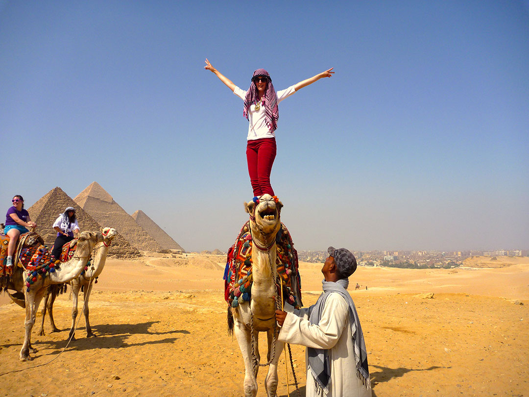 Me standing on the back of Charlie the camel with my hands in the air after racing around the desert in front of the Grand Pyramids of Giza and some other members of the tour group