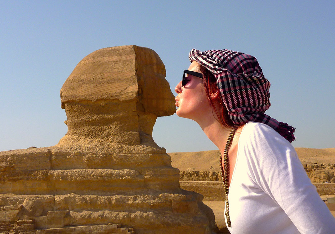 Tacky tourist photo of me pretending to kiss the statue of the Sphinx on a hot summer day while wearing a pink head dress and sunglasses