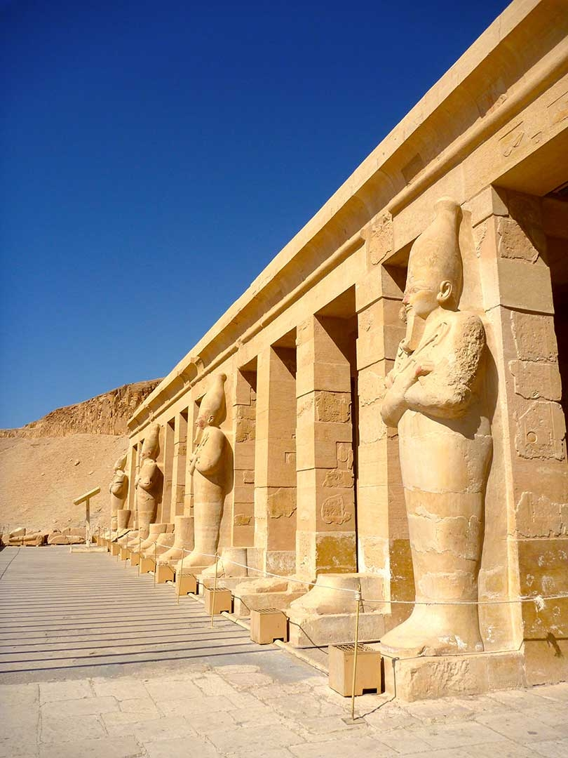 Side view of the front of Hatshepsut's Temple in Egypt with a perfectly blue summer sky