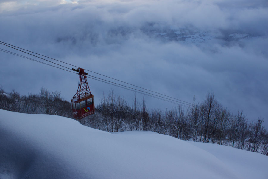 Ski lift above the clouds in Voss, Norway during winter surrounded by snow and bare trees