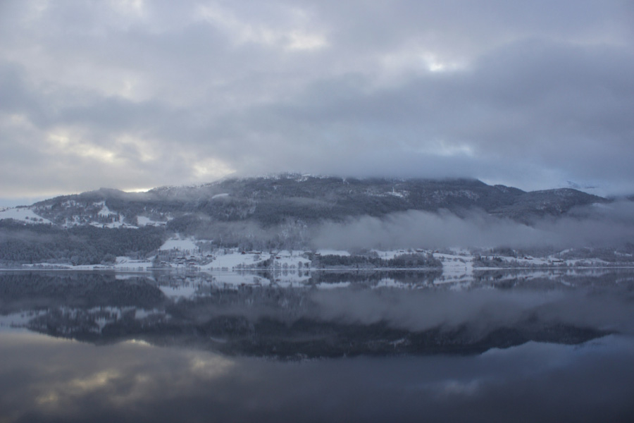 Mountain reflections on the lake in Voss, Norway on a cloudy winter day while on the Norway in a Nutshell self-guided tour