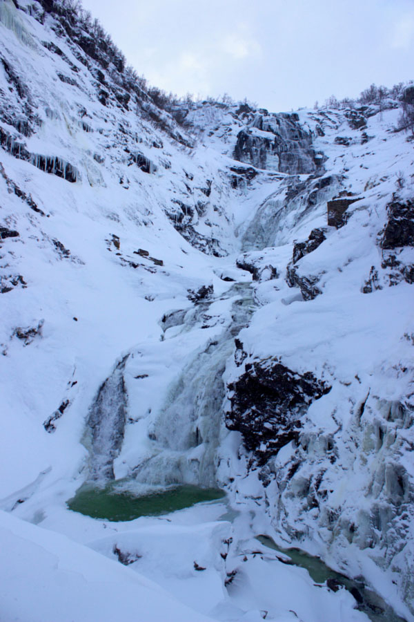 Looking up at Kjosfossen Waterfall covered in snow and partially frozen during winter in Norway on the Norway in a Nutshell self-guided tour