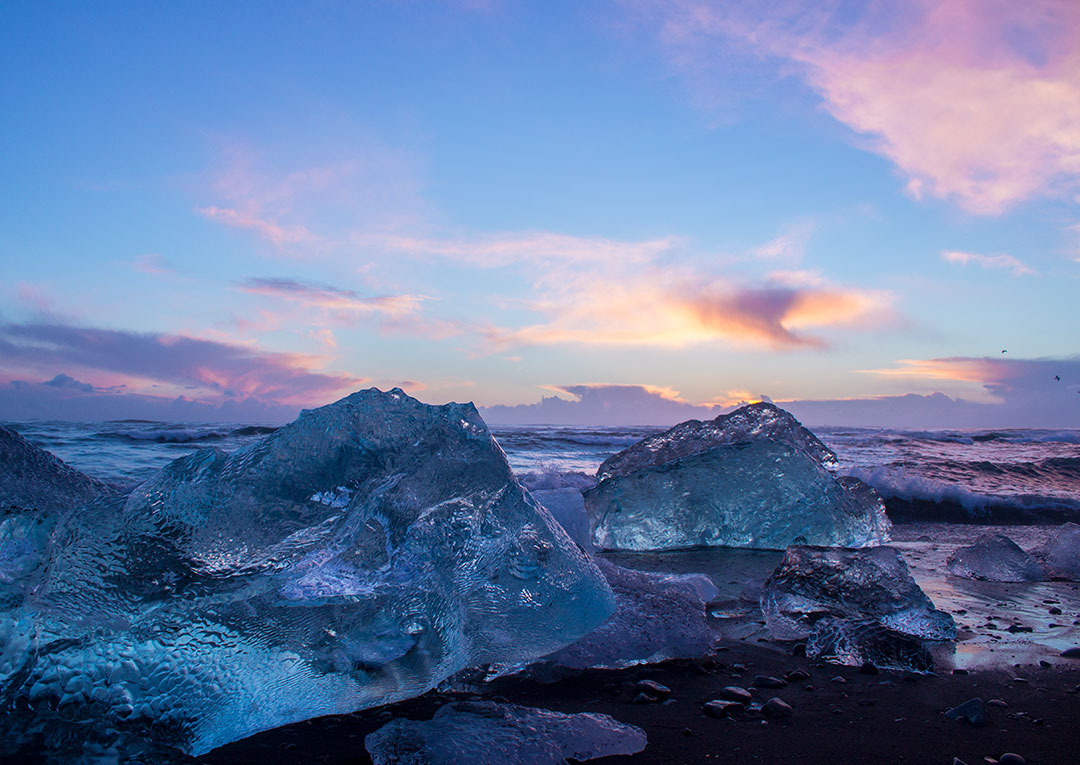 Diamond Beach at Jokulsarlon Glacier Lagoon at sunrise with icebergs on the black sand beach and pink skies