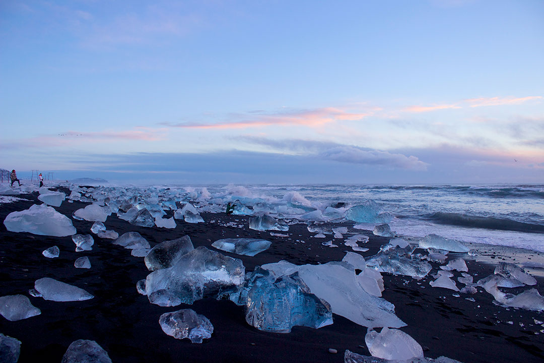 Diamond Beach at Jokulsarlon Glacier Lagoon at sunrise with tiny people standing among icebergs