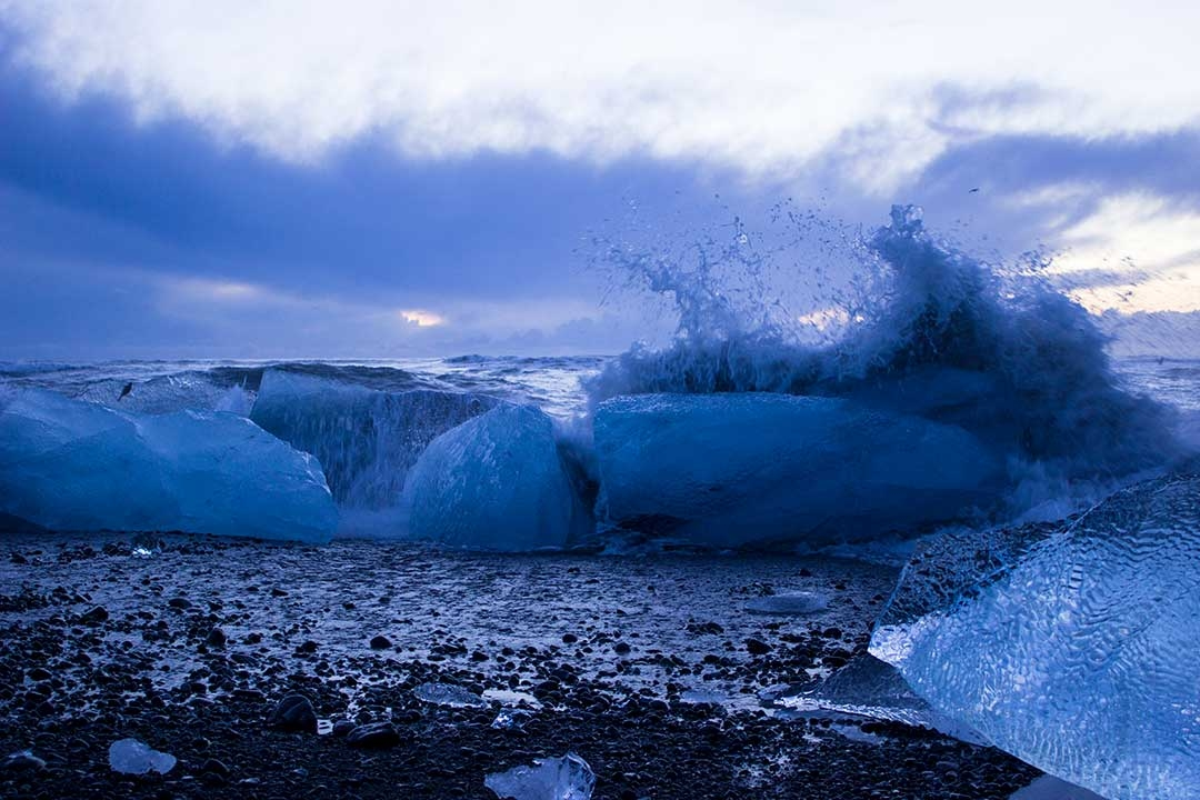 Waves crashing over icebergs on the black sand of Diamond Beach at Jokulsarlon Glacier Lagoon at sunrise