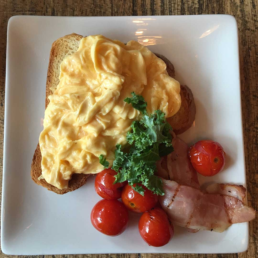 Classic scrambled eggs, bacon and roasted cherry tomatoes on sourdough at Cafe Bang Bang