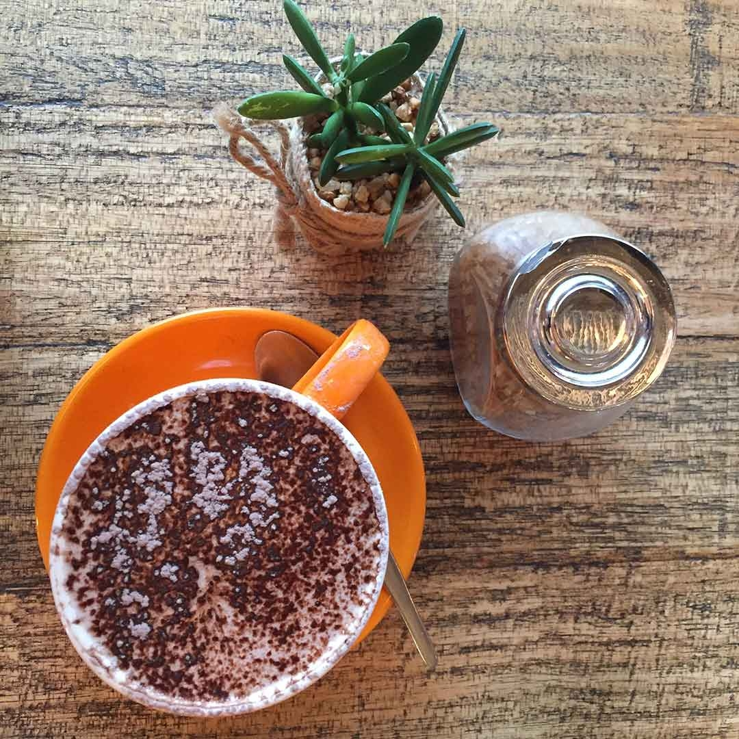 Hot chocolate in a bright orange mug with cute decorations in Cafe Bang Bang